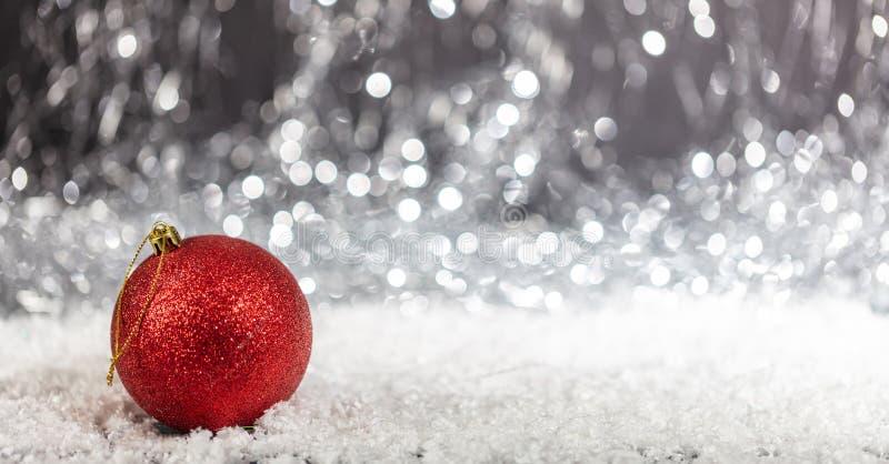 Palla di Natale e neve nella notte, fondo astratto delle luci del bokeh fotografia stock libera da diritti