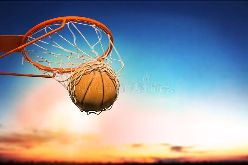 Palla di pallacanestro che cade nella rete sul tramonto immagine stock