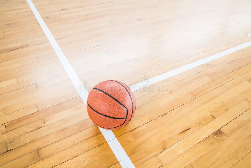 Palla di pallacanestro sopra il pavimento immagini stock libere da diritti