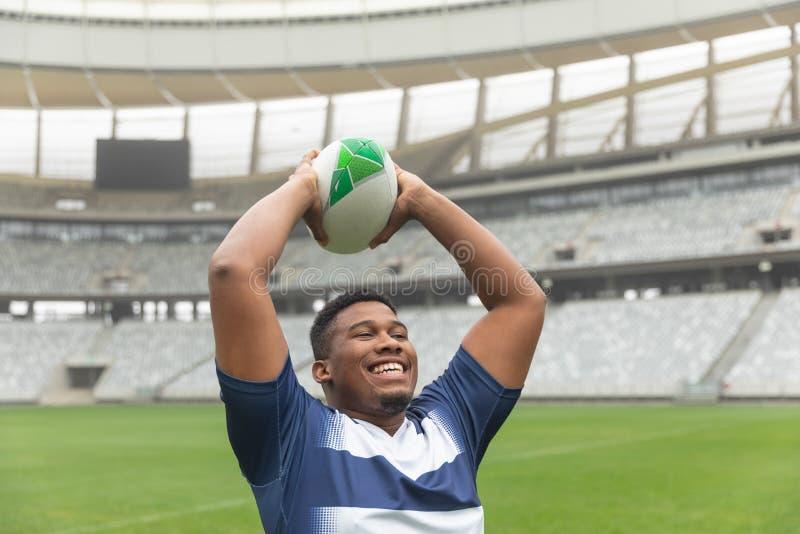 Palla di rugby di lancio del giocatore afroamericano felice di rugby nello stadio fotografia stock