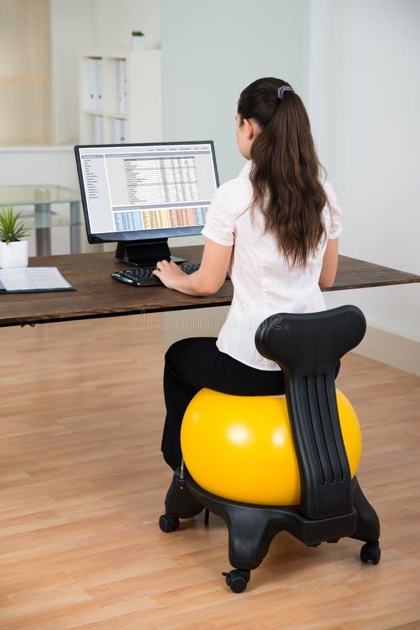 Palla di Sitting On Fitness della donna di affari in ufficio fotografia stock