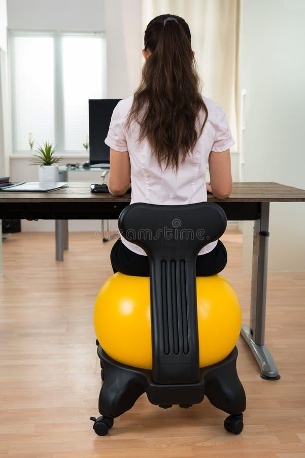 Palla di Sitting On Fitness della donna di affari in ufficio immagini stock libere da diritti