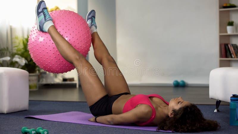 Palla di sollevamento femminile adatta di forma fisica con le sue gambe, forma fisica ed esercitarsi, salute fotografie stock libere da diritti