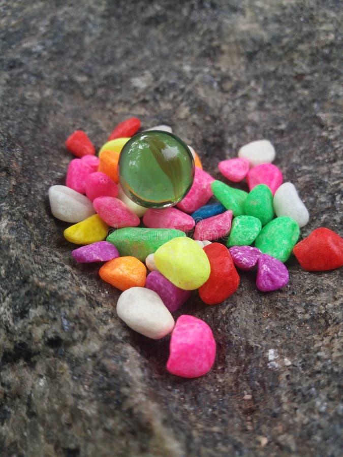 Palla di vetro con le pietre di colore fotografia stock