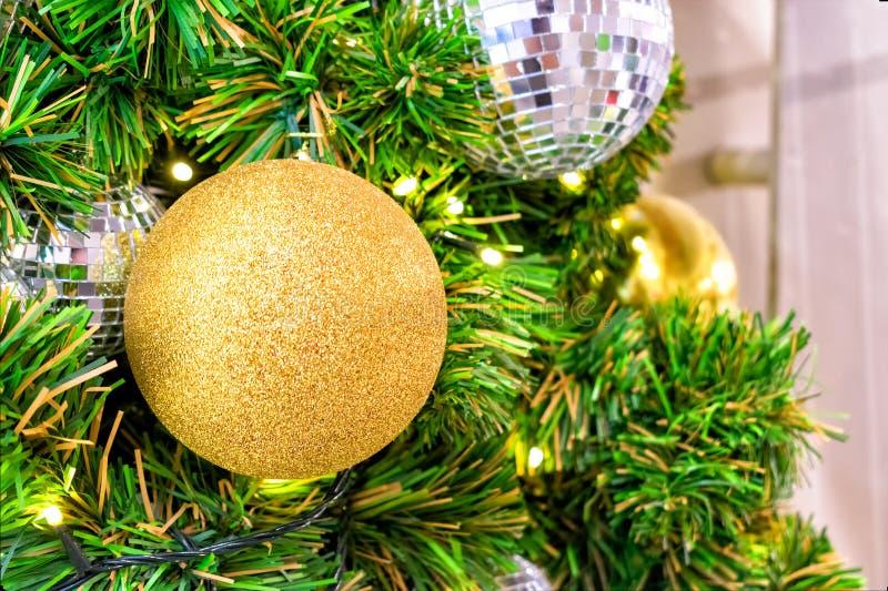 Palla dorata con scintillio come ornamento decorativo di Natale su un albero artificiale fotografie stock libere da diritti