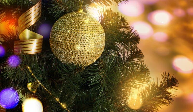 Palla dorata sul ramo dell'albero di Natale immagini stock