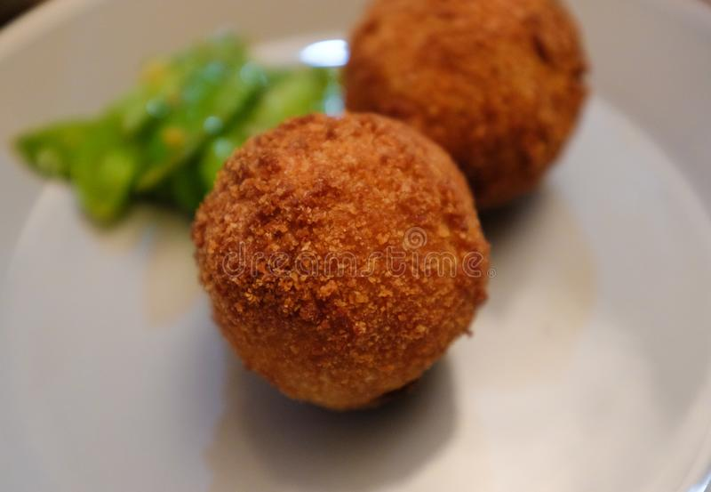 Palla impanata e fritta nel grasso bollente e verdi della patata fotografia stock