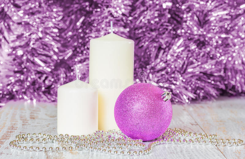 Palla lilla di Natale, due candele bianche e perle d'argento fotografie stock