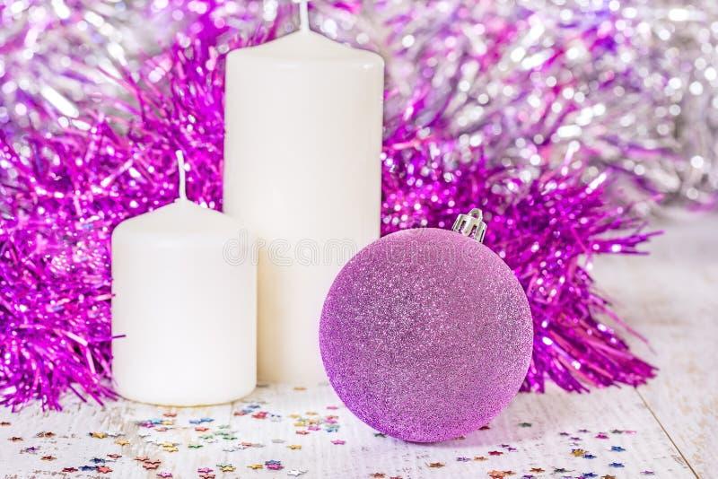 Palla lilla di Natale e due candele bianche fotografie stock