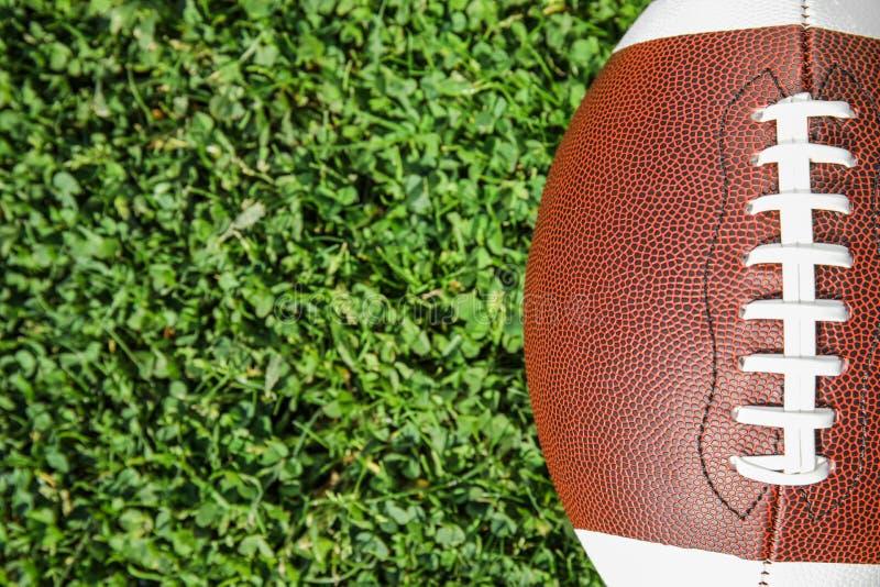 Palla per football americano sull'erba verde fresca del campo, vista superiore immagini stock