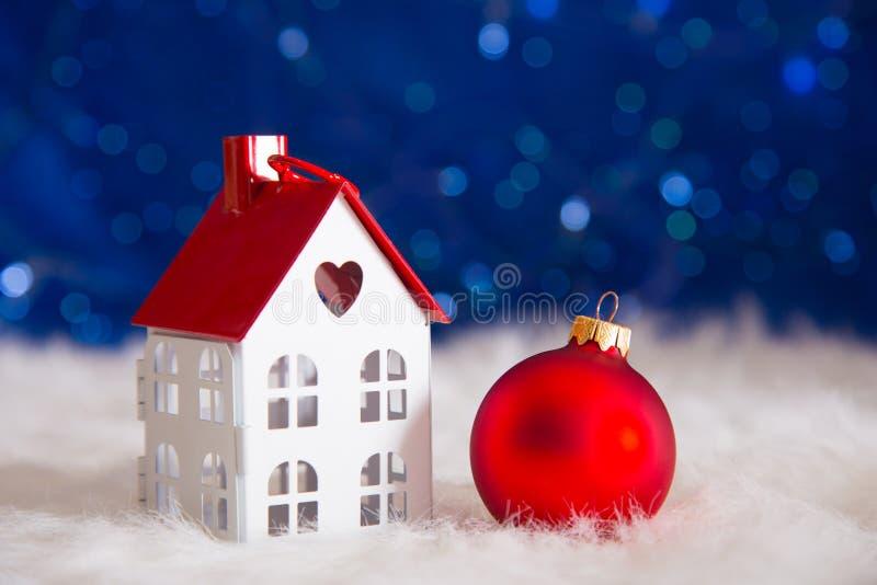 Palla rossa di Natale con il giocattolo poca casa su pelliccia bianca con il garla immagini stock libere da diritti