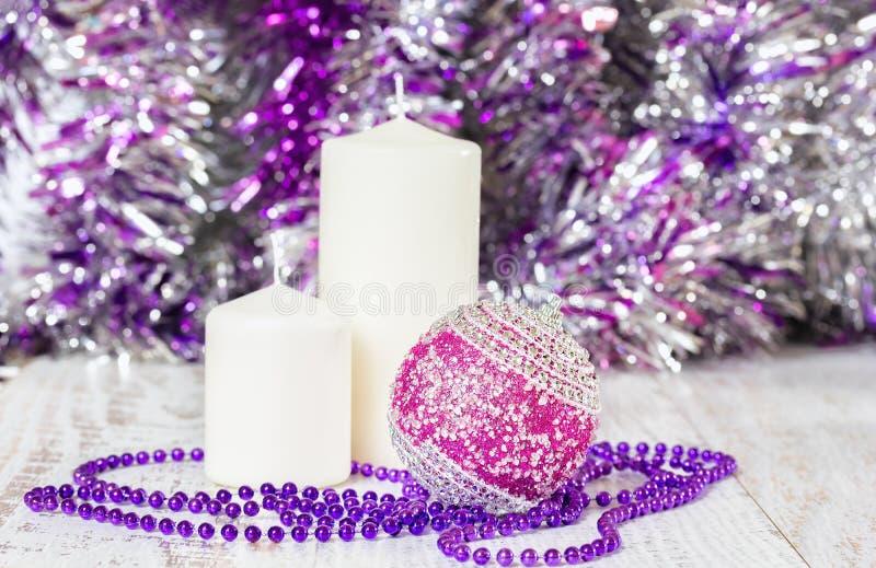 Palla rossa di Natale, due candele bianche e perle porpora fotografia stock libera da diritti