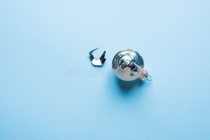 Palla rotta dell'ornamento dell'albero di Natale su fondo blu Schegge che brillano Concetto di speranza di fortuna fotografie stock libere da diritti