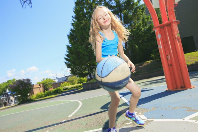 Pallacanestro del gioco della bambina con sul campo da giuoco fotografie stock libere da diritti