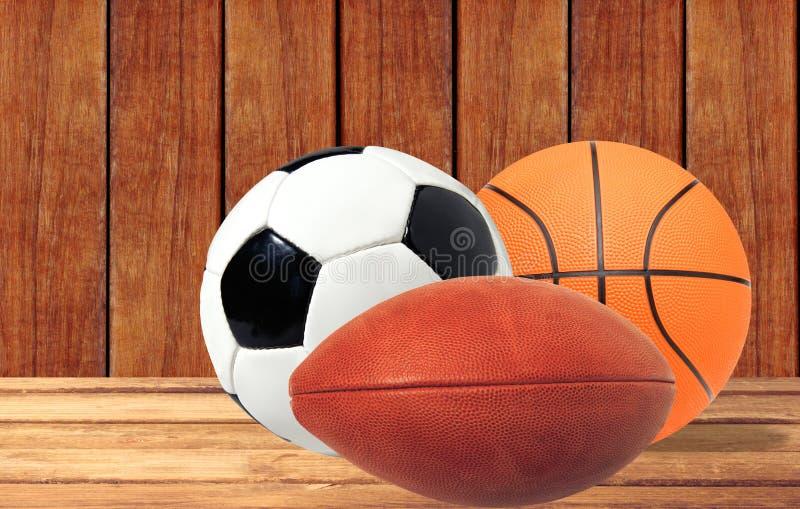Pallacanestro, rugby e pallone da calcio sulla tavola di legno sopra woode fotografia stock libera da diritti