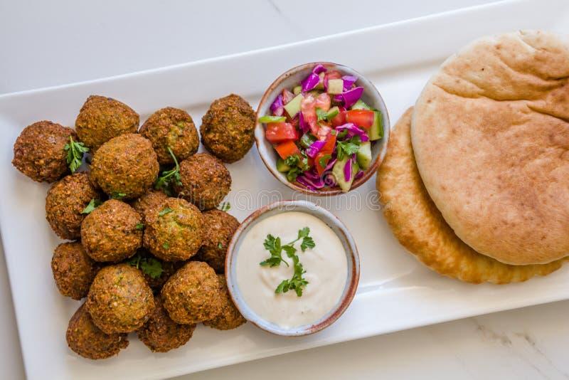 Palle casalinghe del Falafel del cece in un piatto bianco con il pane di pitta della salsa di tahini e dell'insalata contro fondo fotografie stock libere da diritti