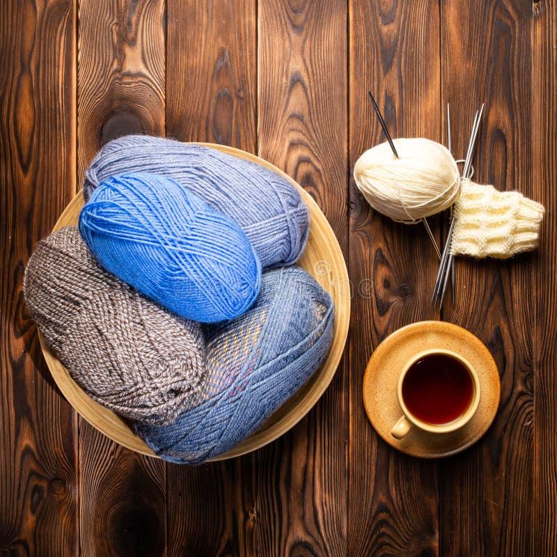 Palle dei fili grigi e blu in piatto, tazza di tè su un piattino e ferri da maglia su un fondo di legno fotografia stock libera da diritti