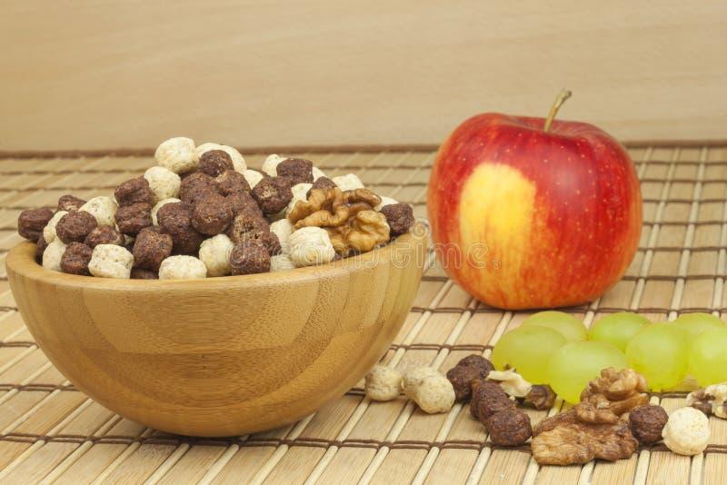 Palle del cereale del cioccolato in una ciotola di bambù Prima colazione sana con frutta e latte Una dieta piena di energia e fib immagini stock libere da diritti