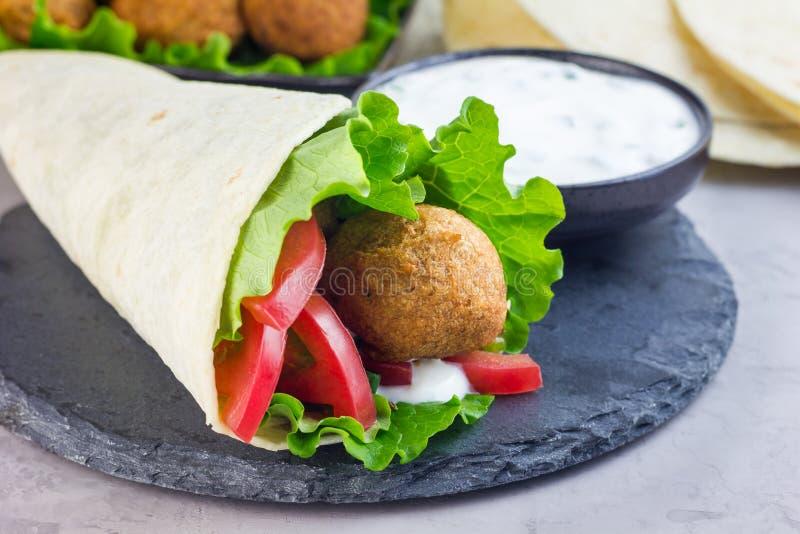 Palle del falafel del cece con le verdure e la besciamella, preparazione del panino del rotolo, orizzontale fotografia stock