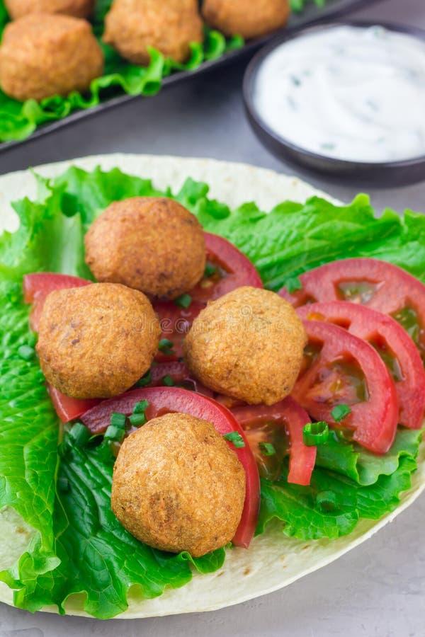 Palle del falafel del cece con le verdure e la salsa, preparazione del panino del rotolo immagini stock libere da diritti