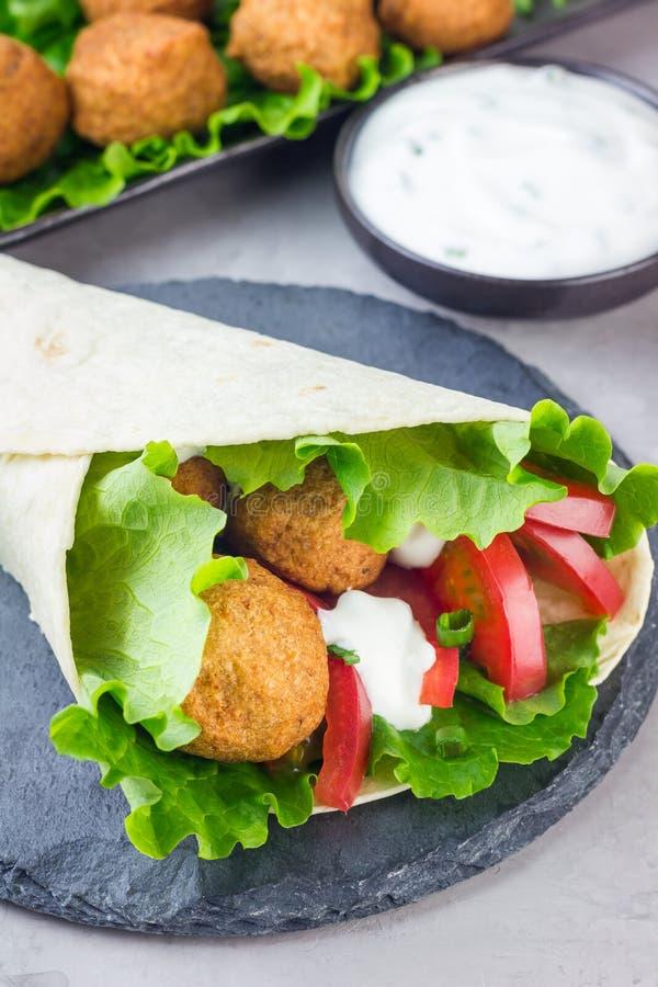 Palle del falafel del cece con le verdure e la salsa, preparazione del panino del rotolo fotografia stock libera da diritti