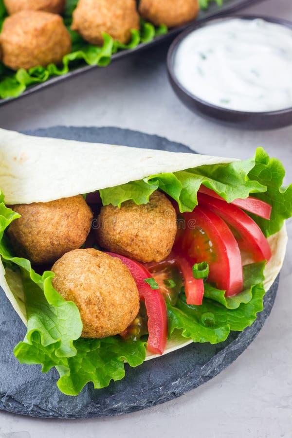 Palle del falafel del cece con le verdure e la salsa, preparazione del panino del rotolo immagini stock