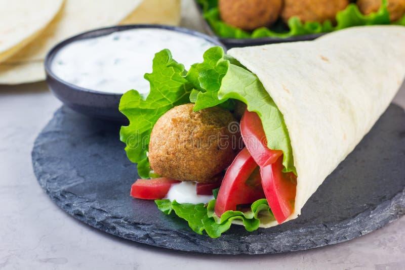 Palle del falafel del cece con le verdure e la salsa, preparazione del panino del rotolo, orizzontale fotografia stock