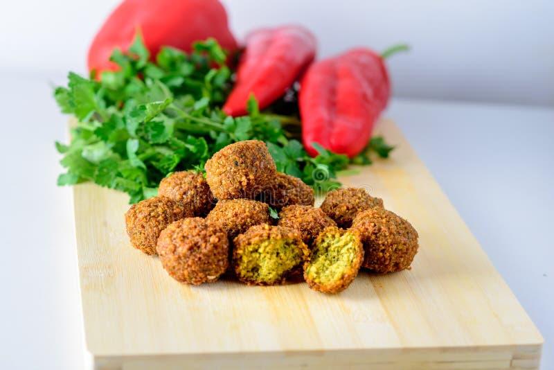Palle del Falafel, peperone dolce e prezzemolo fresco verde su fondo di legno Il Falafel ? un alimento del Medio-Oriente tradizio fotografia stock libera da diritti