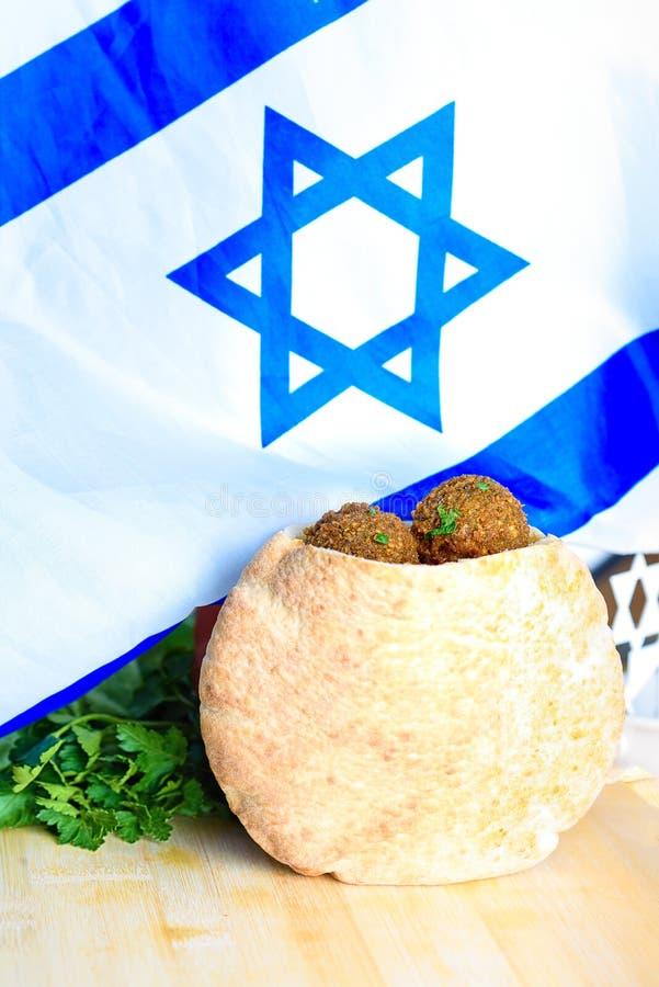 Palle del Falafel in una pita sul fondo di legno della bandiera di Israele della tavola immagine stock libera da diritti