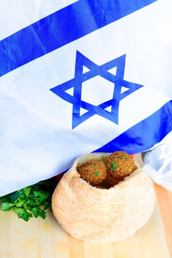 Palle del Falafel in una pita sul fondo di legno della bandiera di Israele della tavola immagini stock