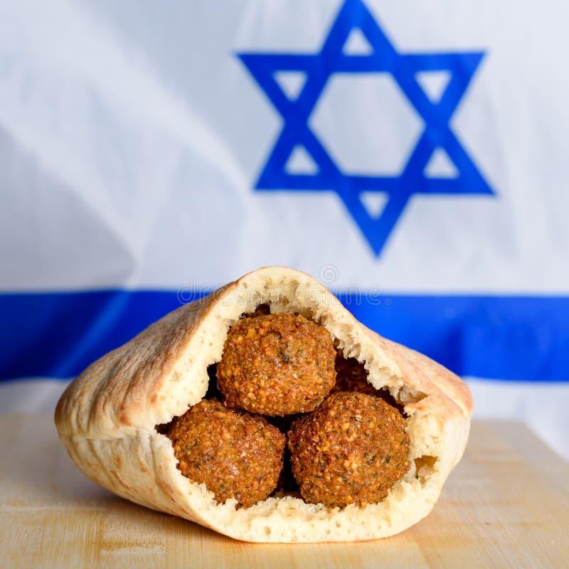 Palle del Falafel in una pita sul fondo di legno della bandiera di Israele della tavola fotografia stock