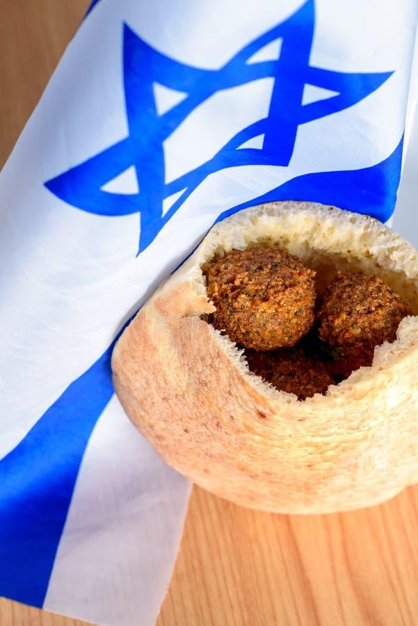Palle del Falafel in una pita sul fondo di legno della bandiera di Israele della tavola fotografia stock libera da diritti