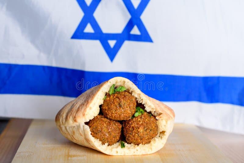 Palle del Falafel in una pita sul fondo di legno della bandiera di Israele della tavola fotografie stock libere da diritti