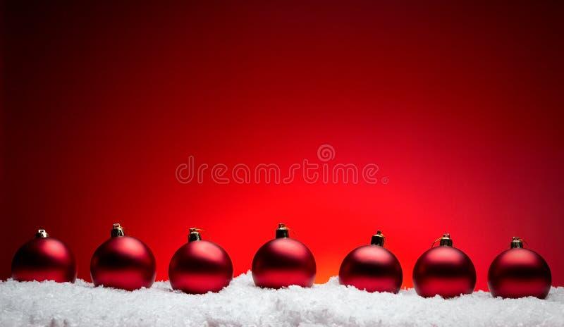 Palle della composizione nel nuovo anno di Natale con la linea di neve backgro di rosso immagini stock