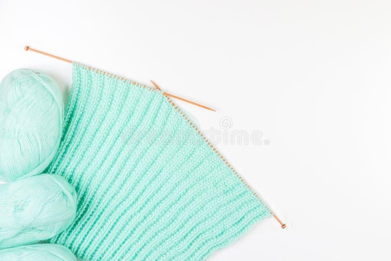 Palle di filato e di tricottare e ferri da maglia differenti di dimensione su fondo bianco fotografia stock