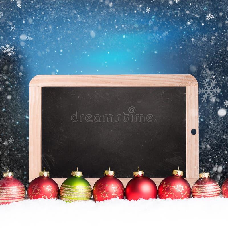 Palle di Natale con la lavagna vuota nella neve fotografie stock libere da diritti
