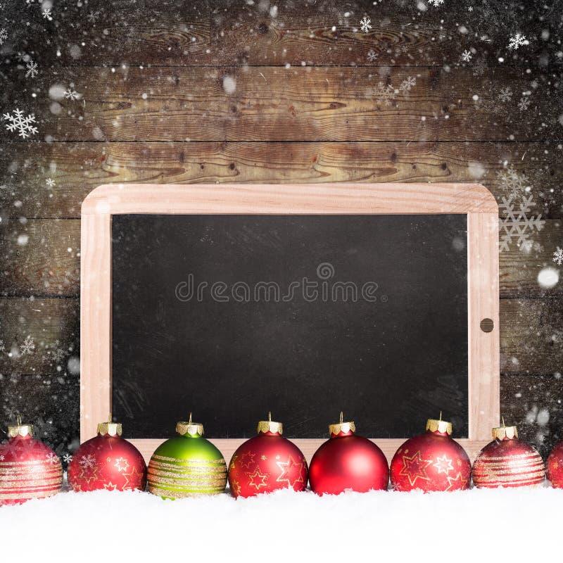 Palle di Natale con la lavagna vuota nella neve immagine stock libera da diritti