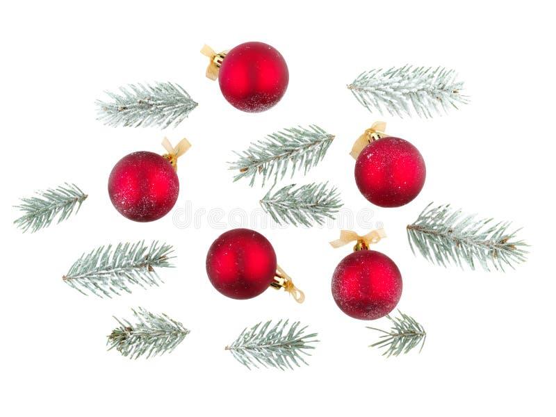 Palle di Natale dei colori rossi con il nastro e ramoscelli degli alberi di Natale Isolato su bianco immagini stock libere da diritti