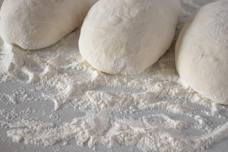 Palle di pasta cruda isolate sulla tavola bianca fotografie stock