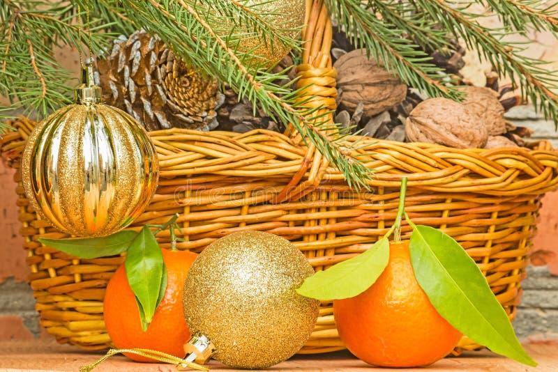 Palle e mandarini di Natale su un fondo di un canestro con fotografie stock