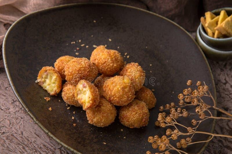 Palle fritte delle patate con carne su fondo nero Spuntino a birra immagini stock