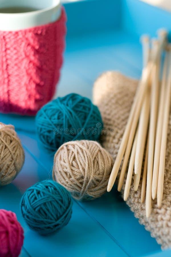 Palle luminose di filato, ferri da maglia di legno, coperta tricottata immagine stock libera da diritti