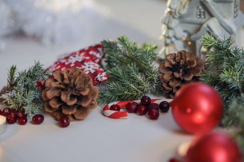 Palle rosse di Natale con il ginepro sulla tavola bianca del fondo e una candela, una congratulazione e una magia brucianti immagini stock