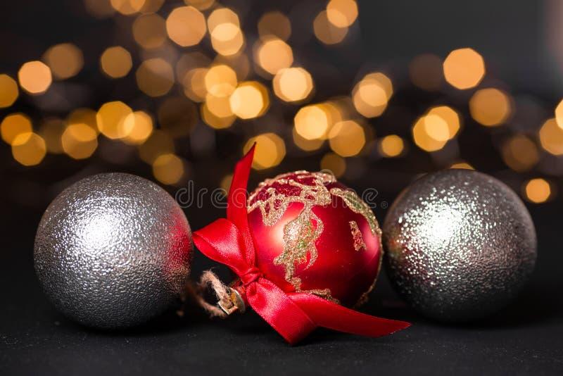 Palle rosse e d'argento di natale su fondo astratto leggero Il Babbo Natale su una slitta Fuoco molle fotografia stock