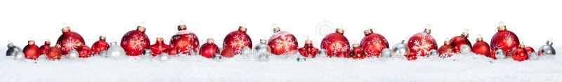 Palle rosse in una fila isolate su neve fotografia stock