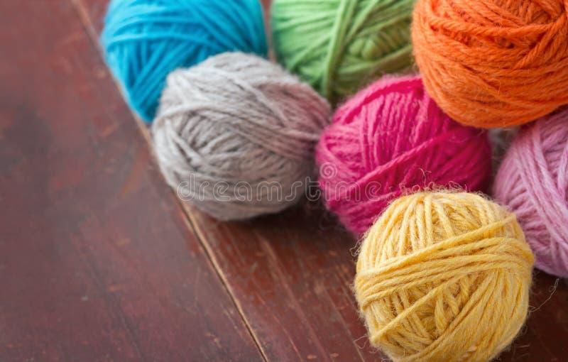 Palle di filato di lana su vecchio fondo di legno fotografie stock libere da diritti