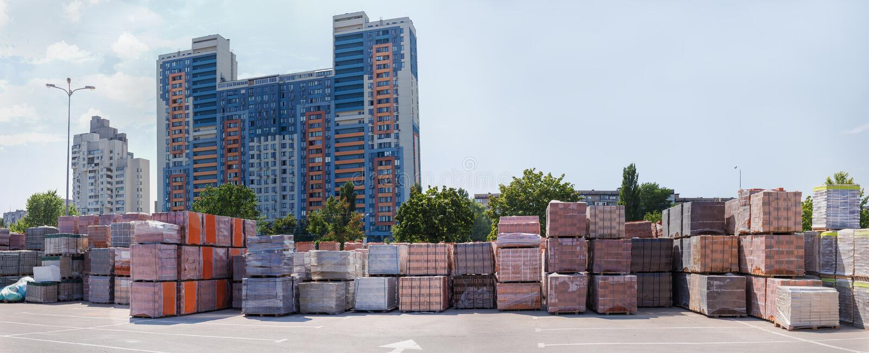 Pallet dei mattoni differenti sul magazzino all'aperto contro delle costruzioni fotografia stock