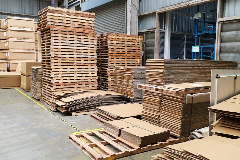 Pallet di legno e scatole di carta nel magazzino della fabbrica fotografie stock libere da diritti