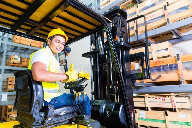 Pallet di sollevamento dell'autista di camion asiatico del carrello elevatore nello stoccaggio immagine stock