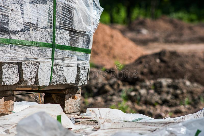 Pallet with granite blocks on the background of a pile of soil and sand royalty free stock image